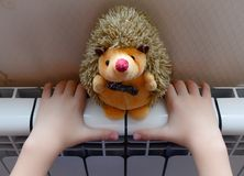 O radiador do aquecimento aquece as mãos da criança Imagens de Stock Royalty Free
