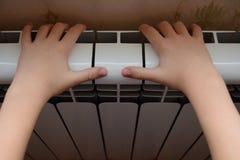 O radiador do aquecimento aquece as mãos da criança Foto de Stock Royalty Free
