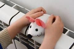 O radiador do aquecimento aquece as mãos da criança Fotos de Stock