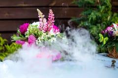 O ramalhete bonito da composição da decoração em uma tabela e o gelo seco fumam fotos de stock