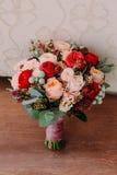 O ramalhete bonito do casamento de flores vermelhas, as flores cor-de-rosa e as hortaliças estão no fundo da parede Imagens de Stock Royalty Free