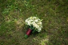O ramalhete branco do casamento com rosas e camomila encontra-se em uma grama fotos de stock