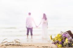O ramalhete das flores na praia com pares borrou o backgroun brilhante Fotos de Stock Royalty Free