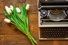 O ramalhete das tulipas brancas e a máquina de escrever no backgound de madeira cobrem v Fotos de Stock Royalty Free
