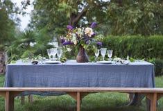 O ramalhete de flores cor-de-rosa, violetas e amarelas em uma tabela ajustou-se para di Imagem de Stock