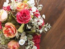 O ramalhete de rosas alaranjadas falsifica em uma tabela de madeira Imagem de Stock