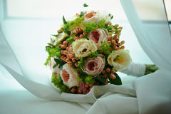 O ramalhete do casamento é forma clássica, com as rosas de creme e cor-de-rosa da peônia, bagas dos botões de ouro na parte de ga Foto de Stock