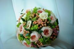 O ramalhete do casamento é forma clássica, com as rosas de creme e cor-de-rosa da peônia, bagas dos botões de ouro na parte de ga Fotos de Stock Royalty Free
