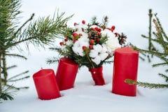 O ramalhete do casamento com algodão e abeto ramifica, as velas vermelhas que estão na neve Foto de Stock