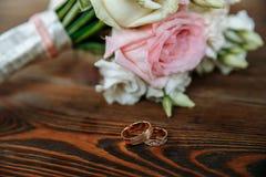 O ramalhete do casamento das rosas de creme e cor-de-rosa encontra-se em uma superfície de madeira Anéis de casamento Fotos de Stock Royalty Free