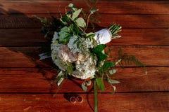 O ramalhete do casamento das rosas de creme encontra-se em uma superfície de madeira Anéis de casamento Imagem de Stock Royalty Free