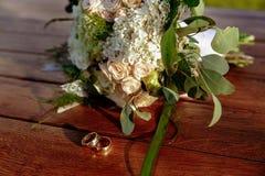 O ramalhete do casamento das rosas de creme encontra-se em uma superfície de madeira Anéis de casamento Imagem de Stock