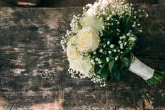 O ramalhete do casamento das rosas de creme encontra-se em uma superfície de madeira Anéis de casamento Fotografia de Stock Royalty Free