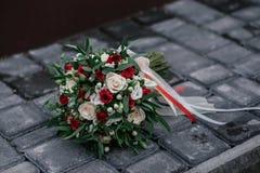 O ramalhete do casamento de mentiras do creme e das rosas vermelhas em pedras surge Fotos de Stock Royalty Free