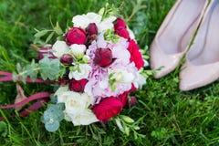 O ramalhete do casamento e as sapatas nupciais elegantes encontram-se em uma grama imagem de stock