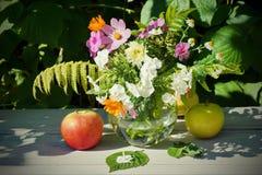 O ramalhete do verão floresce em uma vida de madeira appl maduro da tabela ainda Fotos de Stock