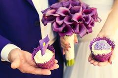O ramalhete e os bolos do casamento são roxos nas mãos Imagens de Stock