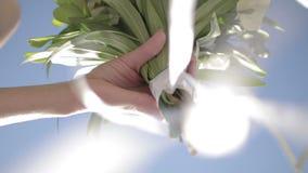 O ramalhete nupcial bonito nas mãos da noiva nova vestiu-se no vestido de casamento branco Feche acima do grupo grande do branco  filme