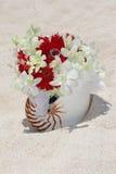O ramalhete nupcial com alianças de casamento em um shell na areia tropical seja Foto de Stock Royalty Free
