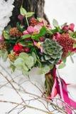 O ramalhete rústico do casamento com plantas carnudas e carmesins floresce na neve ao lado da árvore outdoors artwork imagem de stock