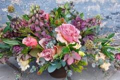 O ramalhete romântico de flores bonitas aproxima a parede velha do grunge fotos de stock