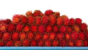 O Rambutan vermelho isolado frutifica indicando na prateleira com fundo branco Foto de Stock
