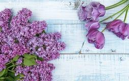 O ramo das flores lilás com um ramalhete de tulipas roxas em um fundo de madeira claro Imagem de Stock Royalty Free