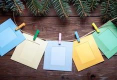 O ramo de árvore do Natal e os pregadores de roupa coloridos com foto moldam o Fotografia de Stock Royalty Free