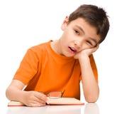 O rapaz pequeno é cansado ler seu livro Imagens de Stock Royalty Free