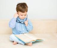 O rapaz pequeno é livro de leitura imagem de stock