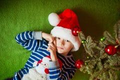 O rapaz pequeno é mentiras perto do abeto Year& novo x27; feriados de s em um t-shirt listrado com Santa Claus Imagens de Stock