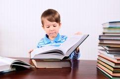 O rapaz pequeno abre um grande livro e a vista nela imagem de stock royalty free