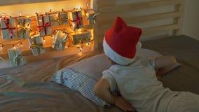 O rapaz pequeno acorda e vê um calendário do advento pendurar em uma cama para iluminar com luzes de Natal Preparar-se para vídeos de arquivo