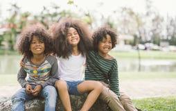 O rapaz pequeno afro-americano bonito e a menina abraçam-se no parque foto de stock royalty free