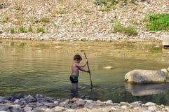 O rapaz pequeno anda em um rio da montanha com uma vara Imagem de Stock