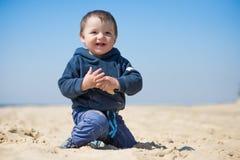 O rapaz pequeno anda na praia Fotos de Stock Royalty Free