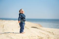O rapaz pequeno anda na praia Fotografia de Stock