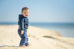 O rapaz pequeno anda na praia Imagem de Stock