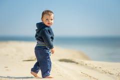 O rapaz pequeno anda na praia Imagem de Stock Royalty Free