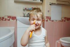 O rapaz pequeno aprende escovar os dentes fotos de stock royalty free