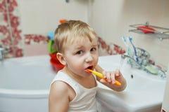 O rapaz pequeno aprende escovar os dentes imagens de stock royalty free