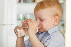 O rapaz pequeno bebe a água imagem de stock royalty free