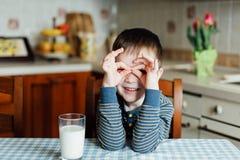 O rapaz pequeno bebe o leite na cozinha na manhã Faz uma máscara com suas mãos Imagem de Stock