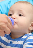 O rapaz pequeno bebe o leite do bebê Fotos de Stock