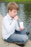 O rapaz pequeno bebe o milkshake Imagens de Stock Royalty Free