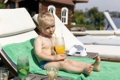 O rapaz pequeno bebe um cocktail imagens de stock royalty free