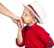 O rapaz pequeno beija a mão da mãe imagem de stock royalty free