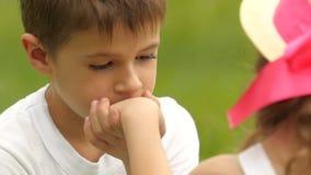 O rapaz pequeno beija a mão do ` s da menina e olha-a Movimento lento vídeos de arquivo