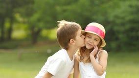 O rapaz pequeno beija a menina no mordente, é embaraçado e sorri Movimento lento video estoque
