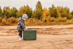O rapaz pequeno bonito abre uma mala de viagem verde velha na roupa retro fotos de stock royalty free